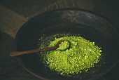 Japanese Matcha green tea powder in dark wooden bowl with spoon