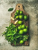 Flatlay of freshly picked organic limes and mint leaves for making cocktail or lemonade on wooden rustic board over grey concrete stone background