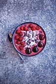 Raspberry smoothie bowl topped with fresh raspberries, cherries, coconut flakes and cacao nibs