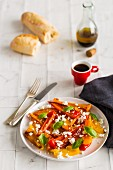A plate of balsamic roasted red, yellow and orange peppers scattered with basil leaves and crumbled goat's cheese