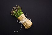 A bunch of British fine asparagus wrapped in brown paper and string on a matt black background