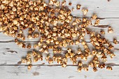 Scattered cinnamon popcorn on a white shabby chic wooden background