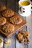 Ginger spelt cookies on a dark wooden board with ground ginger spilled and a mug of golden milk