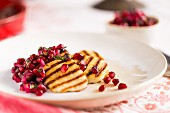 Grilled slices of halloumi on a white plate with pomegranate salsa and mint sprig on a patterened white tablecloth