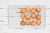 Cooling rack stacked with a grid of heart shaped biscuits on an aged white background