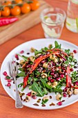 Salad of chickpeas, roasted red peppers, pomegranate seeds and a pomegranate molasses dressing on a white plate with a vintage fork