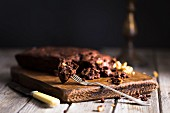 Dark chocolate spelt brownie with walnuts and dates sliced and sitting on a dark wood chopping board with knife and fork
