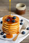 Gestapelte Pancakes mit Ahornsirup begiessen