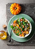 An autumnal salad with pumpkin, salmon, spinach, artichokes, corn and peas