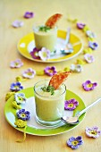 Avocado soup in two glasses with toast and fresh cress, and decorative crochet spring flowers