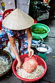 A woman selling bean sprouts at a market in Hoi An, Vietnam