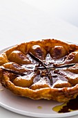 Pear tarte tatin with vanilla pods and puff pastry on a white plate with a white background
