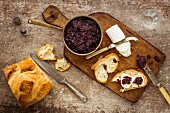 Copper pan filled with red onion chutney on a dark wooden chopping board with crusty bread vintage cutlery and sliced goat's cheese topped with chutney