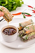 Vegetarian Vietnamese summer rolls filled with smoked tofu, carrot, leaves, sesame seeds, coriander and spring onion stacked on a white plate