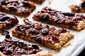 Spelt puff pastry pissaladiere slice with caramelised onions, anchovies and olives on a piece of baking paper on an aluminium metal tray