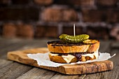 Toasted sourdough cheese sandwich with gherkin, melting, stretched cheese, chutney on an olive wood board