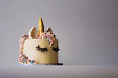 A bespoke made unicorn celebration cake made with multocoloured mane and golden horn