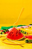 Watermelon slice with yellow plates, tablecloth, cutlery and balloons, along with streamers and straws