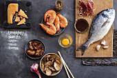 Stillleben mit Parmesan, Garnelen, Anchovis, getrockneten Tomaten, Shitakepilzen, Knoblauch, Ei, Serranoschinken, Sojasauce und Brachse