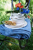 A blue tablecloth, crockery, a bouquet of flowers, and a golden pretzel on a garden chair
