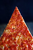 A slice of pizza in front of a dark background (close-up)