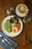 Frühstück mit Avocadobrot, Spiegelei, Tomaten und Tasse Kaffee