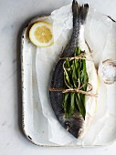 A whole sea bream with wild garlic on baking paper