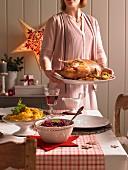 Frau serviert Gänsebraten zu Weihnachten