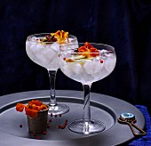 Two glasses of gin and tonic with ice cubes and flowers