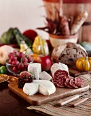 A still life with salami, cheese, autumn fruits and pumpkins