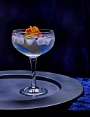 A glass of gin and tonic with ice cubes and flowers