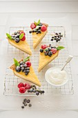 A vanilla tart decorated with fresh berries and cut into slices