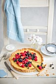 Vanilla tart decorated with fresh summer berries, with a slice cut out