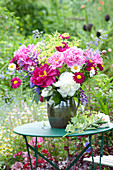 Fruehsommerstrauss auf Tisch im Garten :