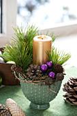 Kleines Kerzengesteck mit Zweigen von Pinus ( Kiefer ), goldener Kerze