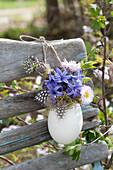 Kleiner Osterstrauß in Entenei als Vase an Stuhllehne gehängt :