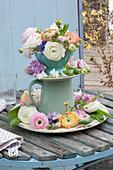 Aus Tellern Schale und Kanne selbstgebaute Etagere mit Blüten