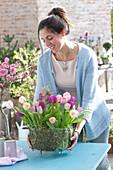 Frau stellt Drahtkorb mit Sträußen aus Tulipa ( Tulpen ) als Deko
