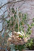 Korbschale mit Gras als hängendes Osternest mit Osterhase und Ostereiern
