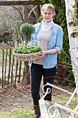 Frau bringt Korbschale mit Thymus vulgaris ( Thymian ) als Stämmchen