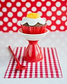 A cupcake decorated with a fondant fried egg