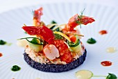 Shrimp and courgette rolls on tomato cream and squid ink