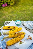 BBQ corn on a cob with herb and pepper butter in a garden