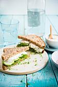 Vollkornsandwich mit Erbsensprossen, Gurke und Kräuterfrischkäse