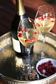 A bottle and two glasses of champagne with wild strawberries on a silver tray