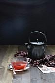 Stillleben mit Teekanne und Kräutertee in Glastasse