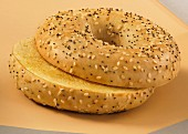 A toasted bagel with sesame and poppy seeds, sliced
