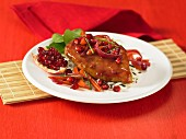 A chicken breast with pomegranate sauce on wild rice