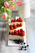 Slices of cheesecake with raspberries and blueberries