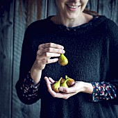 A smiling woman holding fresh figs
